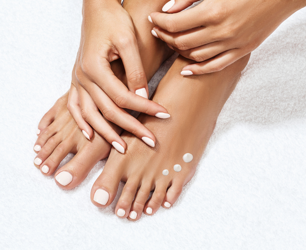 Beautiful female feet with moisturising cream.